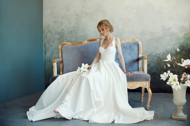 Noiva perfeita, retrato de uma menina em um vestido longo branco. cabelo bonito e pele limpa e delicada. mulher loira de penteado de casamento. menina com uma flor branca nas mãos dela