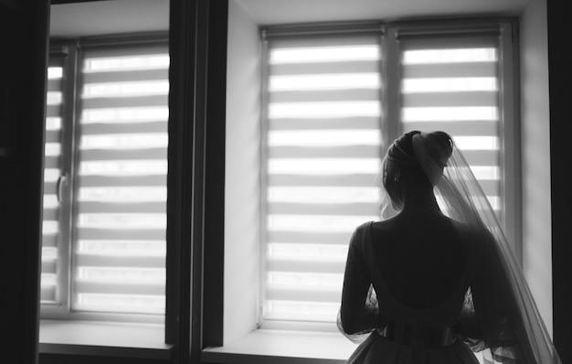 Noiva posando contra a janela mostrando ela de volta