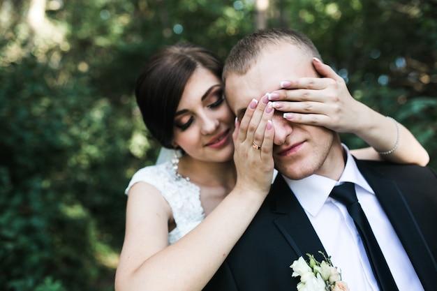 Noiva que cobre os olhos do noivo