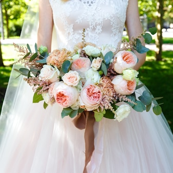 Noiva que prende o ramalhete grande bonito das rosas ao ar livre. moldura quadrada.