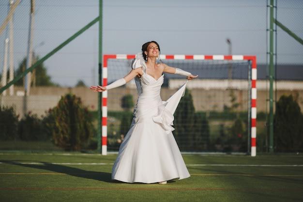 Noiva que sorri em um campo de futebol