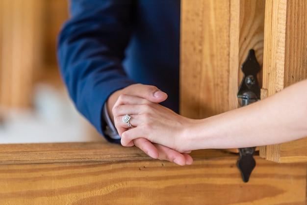 Noiva romântica e noivo de mãos dadas por uma janela aberta