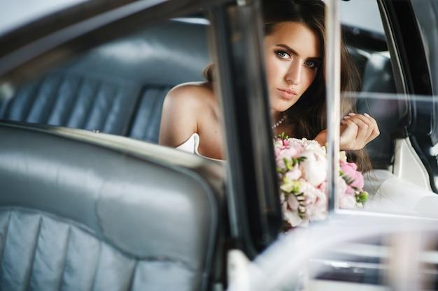 Noiva sedutora senta-se dentro de um carro retrô branco com assentos de couro