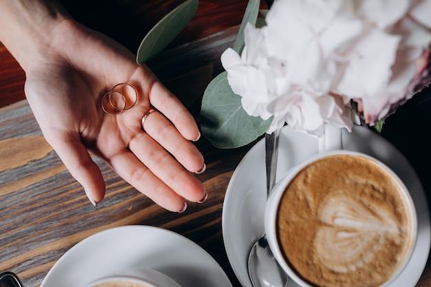 Noiva segura dois anéis de casamento de ouro no braço dela antes de duas xícaras com café