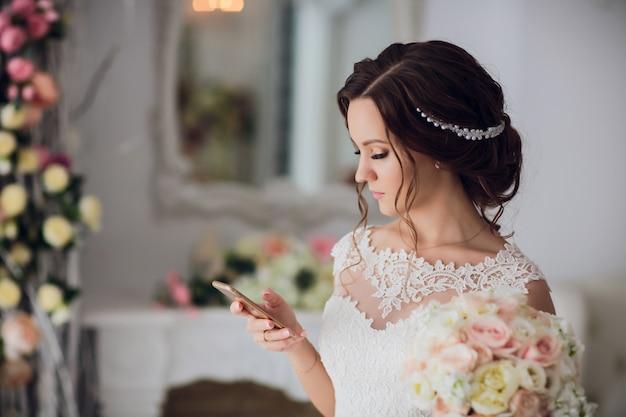 Noiva segura o buquê de rosas e peônias.