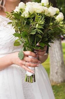 Noiva segura um buquê com rosas brancas