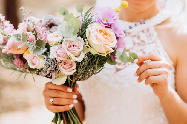 Noiva segura um buquê de casamento. buquê delicado com rosas amarelas e eucalipto.