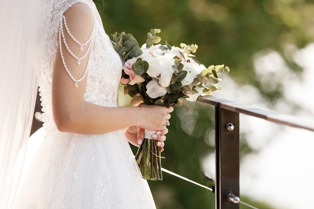 Noiva segura um buquê de flores cor de rosa e brancas