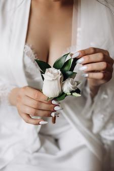Noiva segura um butonholle com rosas