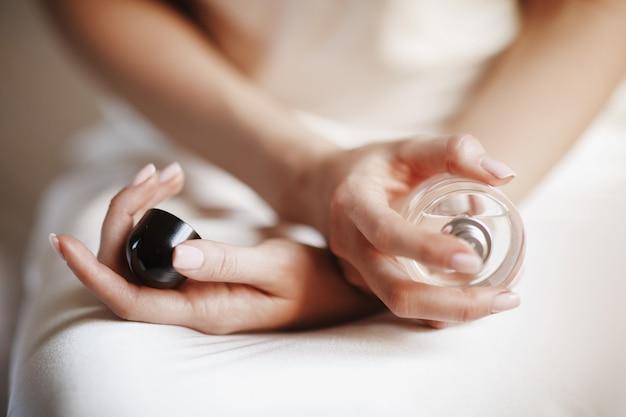 Noiva segura uma garrafa de perfume em seus braços macios