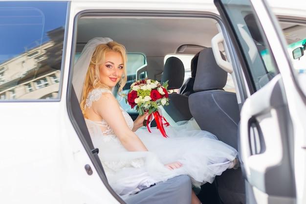 Noiva segurando buquê de casamento em um carro de luxo alugado