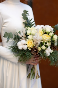 Noiva segurando buquê de pinho, eucalipto, algodão, rosas brancas e lagurus