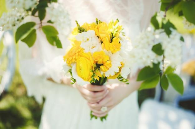 Noiva segurando flores de buquê de casamento