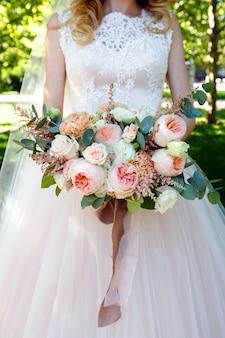Noiva segurando lindo buquê de rosas no parque.
