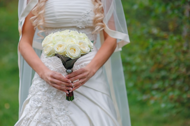 Noiva segurando um buquê branco de rosas e uma flor do amor