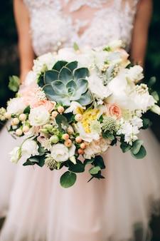 Noiva segurando um buquê de casamento brilhante com flores diferentes