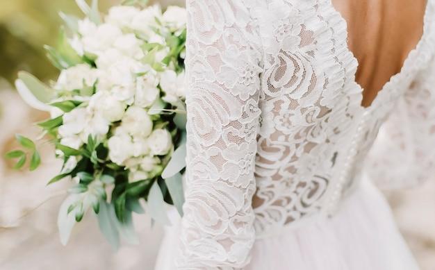 Noiva segurando um buquê de casamento, vestido de noiva branco