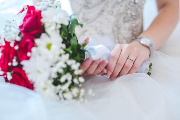 Noiva segurando um buquê de flores rosa e branco