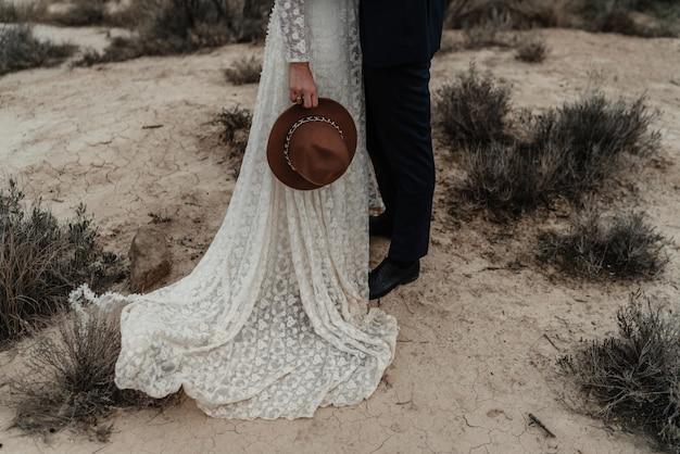 Noiva segurando um chapéu e um noivo em pé perto dos arbustos