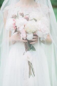 Noiva segurando um lindo buquê de flores de peônia