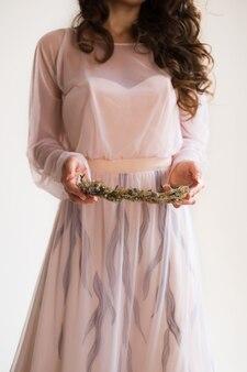 Noiva segurando uma grinalda floral de flores secas. fundo branco no estúdio. manhã da noiva