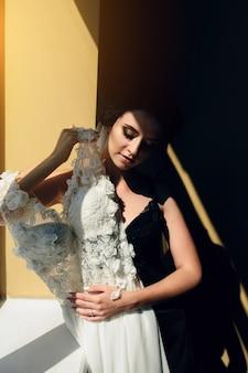 Noiva sentada em uma janela segurando um vestido de noiva