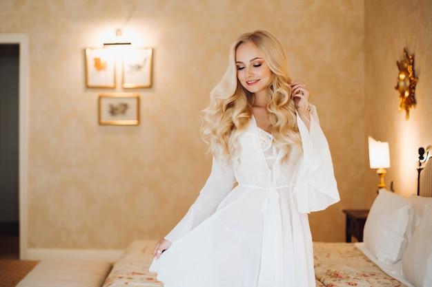 Noiva sexy vestindo lingerie de renda branca no interior do quarto de luxo