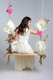 Noiva sorridente na gangorra no estúdio. jovem morena vestido de casamento na gangorra