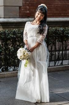 Noiva sorridente posando na rua com buquê