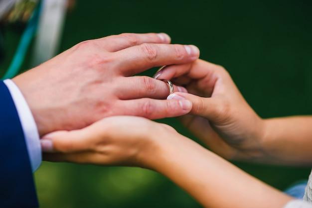 Noiva usa o anel no dedo do noivo na cerimônia de casamento