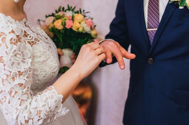 Noiva usa um anel de ouro no dedo do noivo na cerimônia de casamento