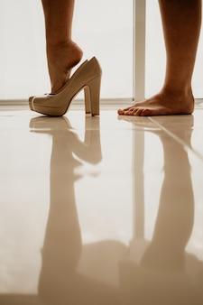 Noiva usando sapato de salto alto no chão do espelho perto da janela panorâmica no dia do casamento