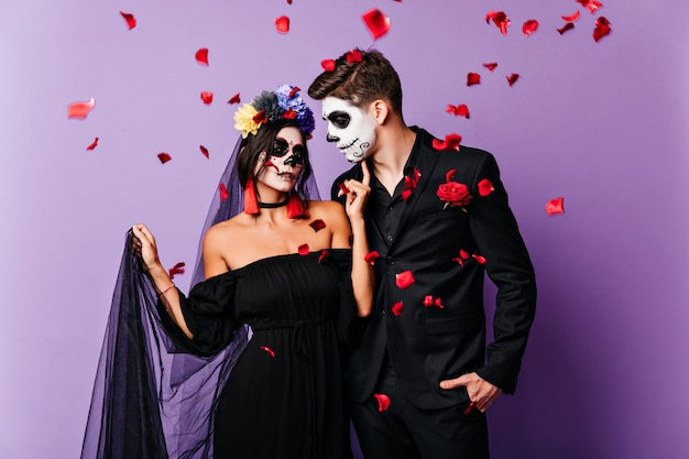 Noiva vampira inspirada posando de vestido preto. casal morto celebrando casamento no halloween.