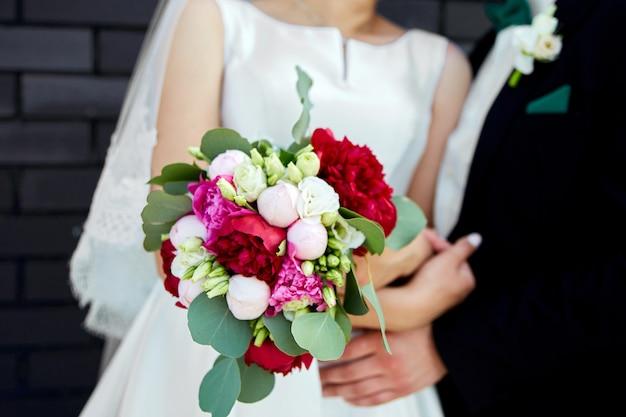 Noiva vestido de noiva e noivo com um buquê de flores e verduras nas mãos.