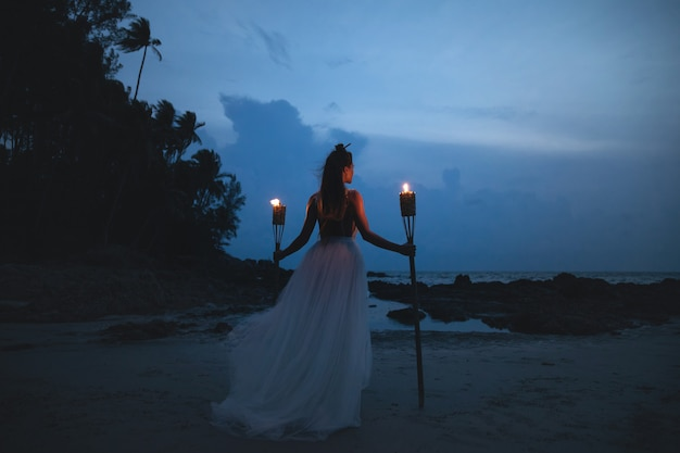 Noiva vestido de noiva lindo está segurando a lanterna na praia