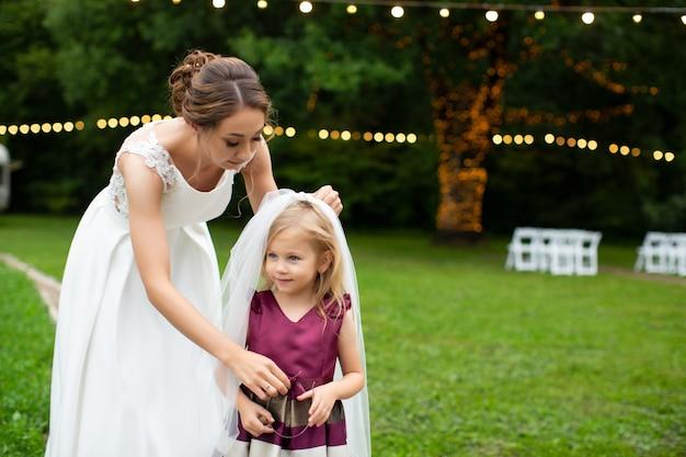 Noiva vestir menina com véu