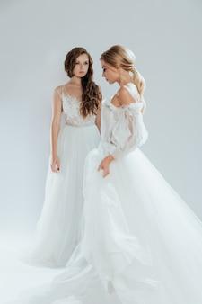 Noivas bonitas com maquiagem e penteado de casamento e vestidos longos brancos