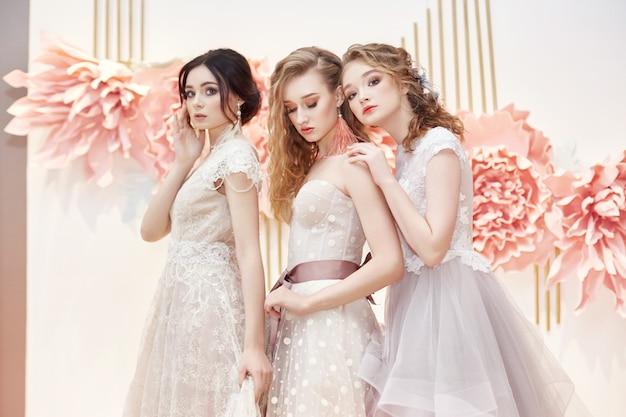 Noivas bonitas do trio no vestido de casamento caro
