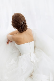 Noivas de beleza. jovem mulher no vestido de casamento dentro de casa