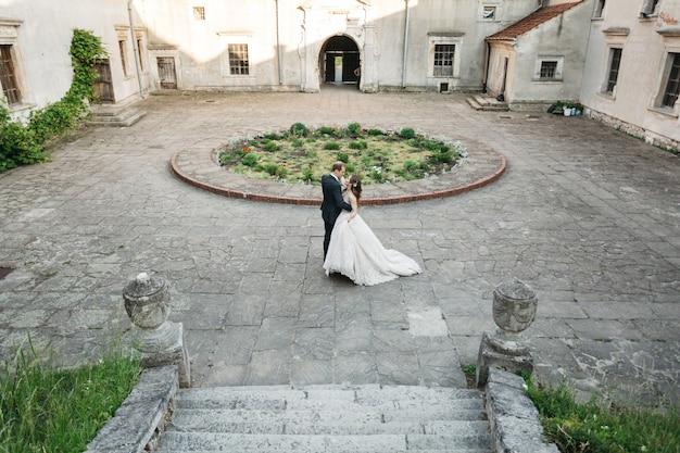 Noivas felizes dançar perto do castelo