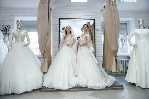 Noivas felizes em vestidos de noiva posando no salão