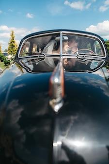 Noivas felizes estão se beijando no carro