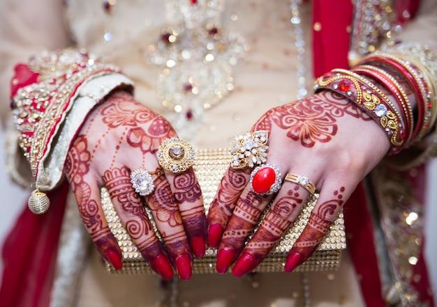 Noivas indianas paquistanesas mãos mostrando anéis e jóias com embreagem