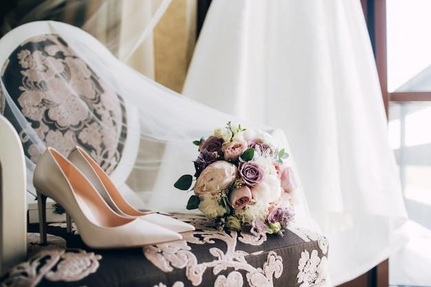 Noivas, sapatos de casamento com um buquê de rosas e outras flores na poltrona tha