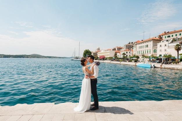 Noivo abraça a noiva em um vestido de renda branca com um buquê de lavanda nas mãos, em pé no cais perto