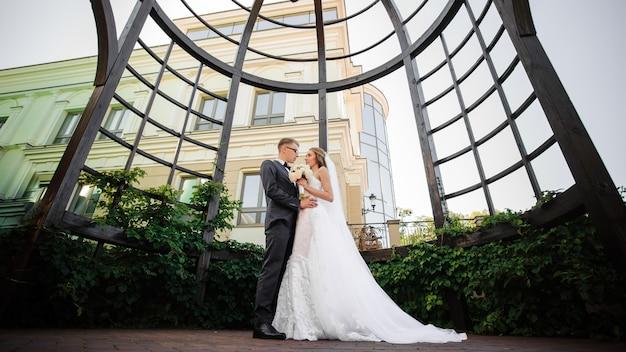 Noivo abraça a noiva em um vestido de renda branca com um buquê na cena da estufa