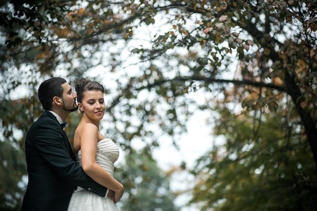 Noivo abraça gentilmente a noiva com um buquê por trás em um parque Foto Premium