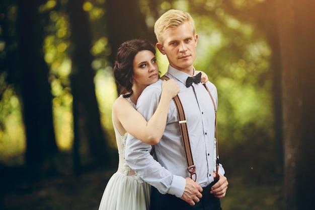 Noivo abraça gentilmente seu noivo na floresta