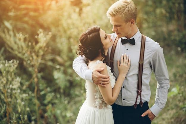 Noivo abraçando gentilmente sua noiva na floresta