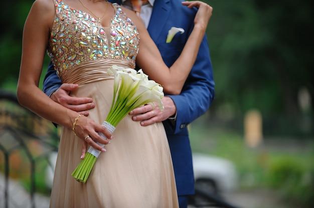 Noivo, abraçando, noiva, com, buquê casamento, de, branca, lírios calla